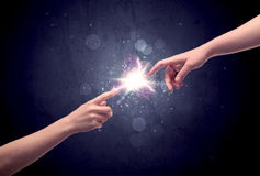 Hands reaching to light a spark Royalty Free Stock Photography
