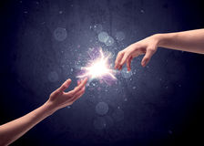 Hands reaching to light a spark Stock Photo