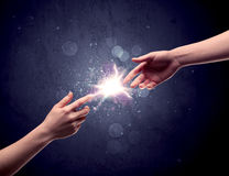 Hands reaching to light a spark Royalty Free Stock Images