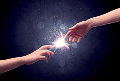 Hands reaching to light a spark Stock Images