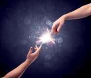 Hands reaching to light a spark Stock Photos