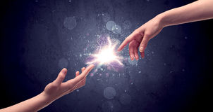 Hands reaching to light a spark. Two male hands reaching towards each other, almost touching with fingers, lighting spark in galaxy background concept royalty free stock photography