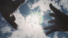 Hands reaching to sun, striving for God, looking for answer in skies above slow