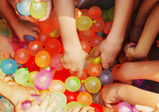 Hands reaching for water balloons Stock Photo
