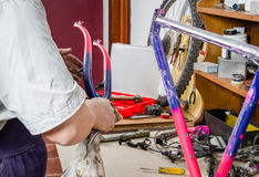 Hands of real bicycle mechanic cleaning frame bike Royalty Free Stock Photos