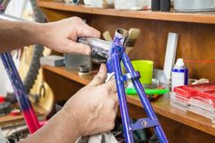 Hands of real bicycle mechanic sanding frame bike Stock Image