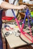 Hands of real bicycle mechanic sanding frame bike Stock Photos