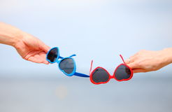 Hands with red and blue sunglasses shaped heart Stock Image