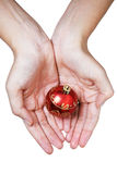 Hands and Red Christmas Bauble Stock Photos