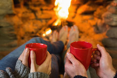 Hands with red coffee cups in front of lit fireplace Royalty Free Stock Images