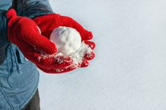 Hands in red gloves holding snowball. On the snow background. Winter season, vacation, games concept. Copy space royalty free stock image