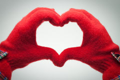 Hands in red gloves show heart shaped sign Stock Photography