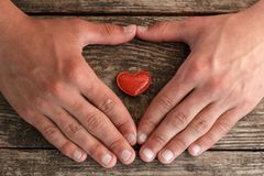 Hands and a red heart lying on a wooden background, concept of health stock photography