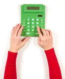 Hands in red jacket and green calculator Stock Images