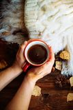 Hands in red knitted gloves holding a hot cup of coffee against yellow leaves background. Concept of autumn time, warmth and cozin. Woman warming his hands on a royalty free stock image