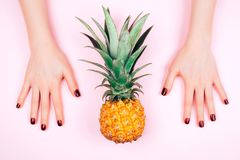 Red manicure on pink background with pineapple stock photo