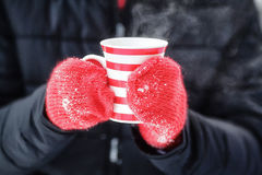 Hands in red mittens holding hot winter mug with steam Royalty Free Stock Photo