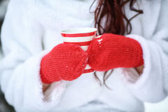 Hands in red mittens holding hot winter mug with steam Royalty Free Stock Photography