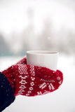 Hands in red mittens holding a mug of tea Royalty Free Stock Image