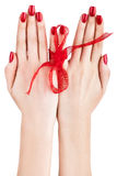 Hands with red ribbon. Royalty Free Stock Photos
