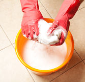 Hands with red rubber gloves and bucket Stock Photo