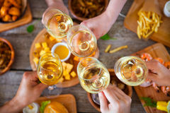 Hands with red wine toasting over served table with food. Stock Photo