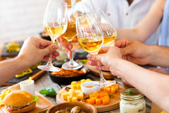 Hands with red wine toasting over served table with food. royalty free stock photography