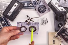 Hands reeling tape back into audio compact cassette Stock Images