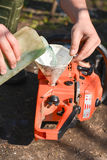 Hands refilling the chainsaw with fuel Stock Photography