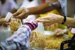 Hands of Refugees Receive Humorous Charity Food : The Concept of Food Shortage.  stock photography