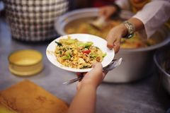 Hands of Refugees Receive Humorous Charity Food : The Concept of Food Shortage.  royalty free stock images