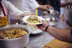 Hands of Refugees Receive Humorous Charity Food : The Concept of Food Shortage.  royalty free stock image