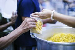 Hands of Refugees Receive Humorous Charity Food : The Concept of Food Shortage.  stock photos