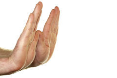 Hands Refusing. Adult male hands seen from the side with palms raised up in a stop gesture in front of a white background Royalty Free Stock Images