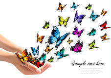 Hands releasing colorful butterflies. Stock Image