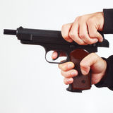 Hands reload semi-automatic gun on white background Royalty Free Stock Image
