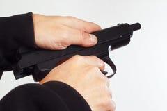 Hands reload semi-automatic handgun on white background Stock Photo