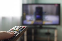 In the hands of the remote from the TV, in the background comes the TV television stock photos