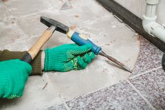 Hands remove tile with chisel and hammer. Dismantling of tile. Hands in green working gloves undermine the tile with a chisel and a hammer stock photos