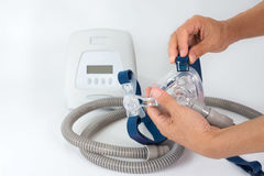 Hands removing clip from headgear, full components of Cpap system, isolated white background. Cpap Continuous positive airway pressure system includes of main royalty free stock photography