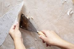 Hands removing old wallpaper with the help of a spatula during t. He repair in the room. Close-up stock image