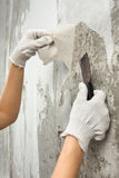 Hands removing old wallpaper with spatula during repair Stock Photos
