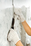 Hands removing wallpaper from wall with spatula Royalty Free Stock Photos