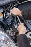 Hands repairing a car engine with a wrench. Two hands tightening a bolt in a modern car engine with a wrench Royalty Free Stock Image
