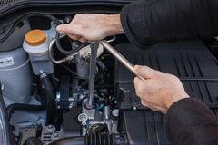 Hands repairing a car engine with a wrench. Two hands tightening a bolt in a modern car engine with a wrench Royalty Free Stock Photos