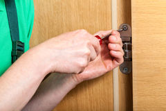 Hands repairing a door hinges Stock Photo