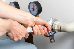 Hands repairing valves in boiler room Stock Image