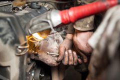 Hands of repairman mechanic working on engine using tool Royalty Free Stock Image