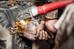 Hands of repairman mechanic working on engine using tool. Close-up detail shot of car mechanic dirty hands. Worker repairing broken motor in garage using socket Royalty Free Stock Image
