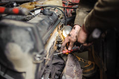 Hands of repairman mechanic working on engine using tool Royalty Free Stock Images